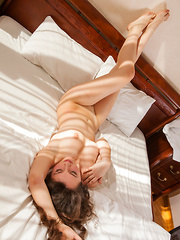 Sweet-smiling Conchita with her pretty face and voluptuous body posed naked on top of the bed